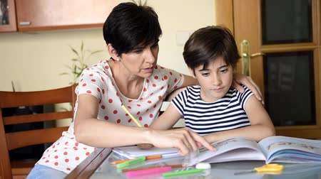 Middle-aged mother helps her daughter with her homework. Stok Video
