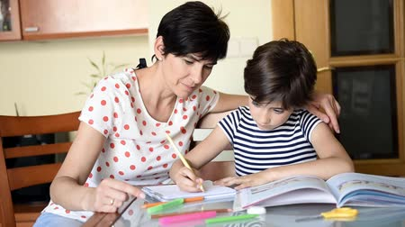 ders kitabı : Middle-aged mother helps her daughter with her homework. Stok Video