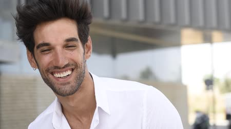 spanish style : Young man smiling to camera wearing casual clothes with modern hairstyle. Stock Footage