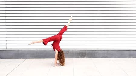 Redheaded fit woman doing fitness acrobatics in urban background.