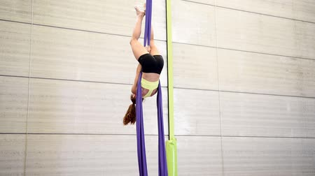 dokular : Young redheaded woman doing aerial gymnastic acrobatics with acrobatic fabrics inside a gym.