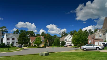 low lighting : Time lapse of idyllic suburbs with homes on a cul de sac and rolling cumulus clouds on a sunny day timelapse Stock Footage