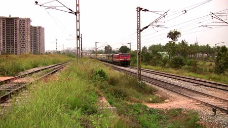 tava : BANGALORE, KARNATAKA, INDIA - DEC 12, 2007. Indian passenger train passes at high speed in the suburbs of Bangalore. Stok Video
