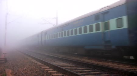 bangalore : BANGALORE, KARNATAKA, INDIA - DEC 12, 2007. Indian passenger train passes by at high speed in the foggy winter morning in the suburbs of Bangalore, Karnataka, India. Stock Footage