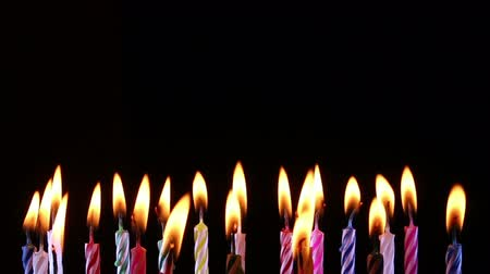 cera : birthday candles light on isolated black
