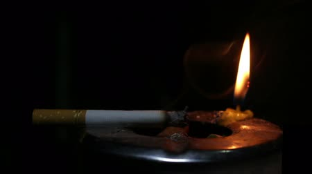 smettere di fumare : cigarette burning and candle light Filmati Stock