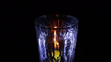 candle light with glass isolated black Stock mozgókép