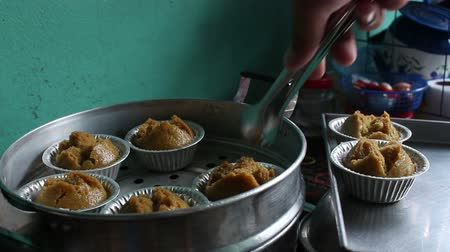 picking brown cupcake from Steaming pot