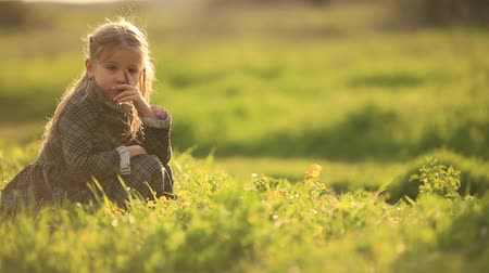 bídný : Young Sad Girl Lonely in Grass Field. a young girl is sitting on a grass field, frustrated or sad.