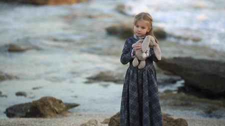 peluş : Little dreaming girl wearing elegant dress while embracing small soft bunny toy standing on coast