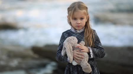 плюшевый мишка : Little cute girl with blond hair, stands against the sea in cold weather. Girl playing with teddy bear Стоковые видеозаписи