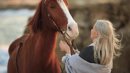 equestre : Young Blonde Girl with long hair Stroking and Hugging a Horse. Horse on the seashore enjoying nature. Love and friendship concept
