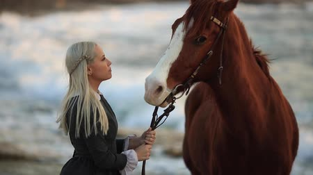 okşayarak : Young Blonde Girl with long hair Stroking and Hugging a Horse. Slow motion. Horse on the seashore enjoying nature. Love and friendship concept.