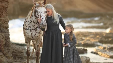 benekli : Therapy with horses - hippo therapy. Woman in classic dress and mottled horse