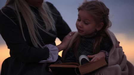 pléd : Woman with girl reading book on seashore. close-up full hd