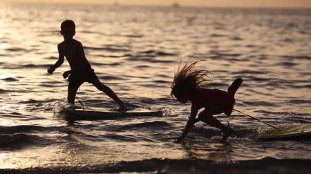 доска для серфинга : Happy children playing on the beach at the sunset time. Concept of summer vacation, friendly family