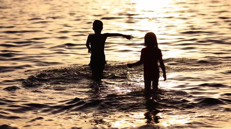 outside : Happy children playing on the beach at the sunset time. Concept of happy friendly family