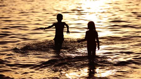 sensibilidad : children walking by the sea at the sunset time Archivo de Video