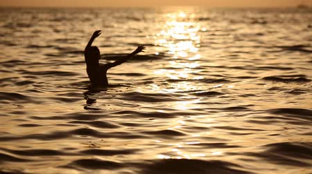 armoni : Boy having fun in sea at sunset, search of physical and spiritual harmony on planet Earth. Stok Video