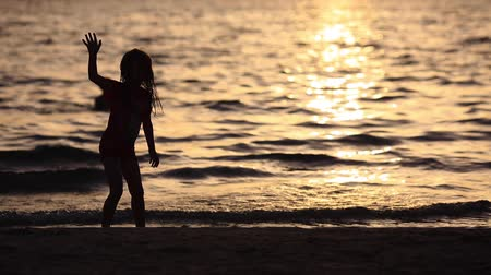 gimnastyka : cute little 5 year old gymnast practices golden sunset at the beach