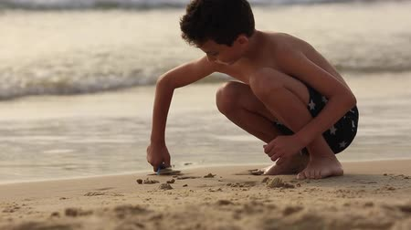 eski : boy playing with sand on the sea Stok Video