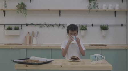ニュートラル : Boy eat cookie with milk. White Table in Kitchen. Cookies with milk. neutral color video