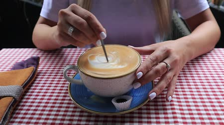 adoçante : female hands with a spoon stirs sugar in coffee