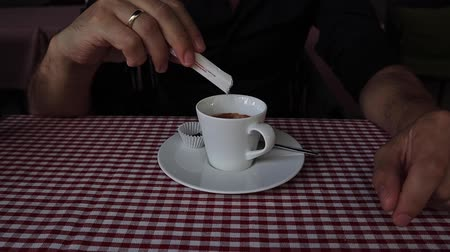 sweetener : Mans hand pouring sugar into cup with cappuccino slow motion Stock Footage