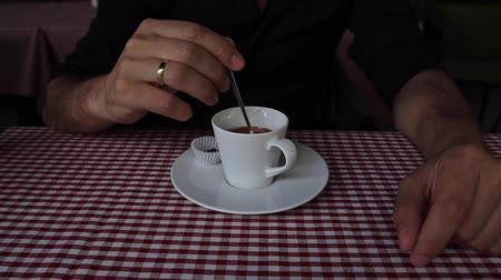 grãos de café : Focus on man hand holding spoon in cup of coffee