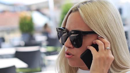 discutir : Young blonde in sunglasses, close-up view from the side talking on a cell phone in an outdoor cafe.