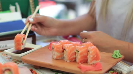 икра : Young woman in cafe eating sushi with chopsticks. close-up
