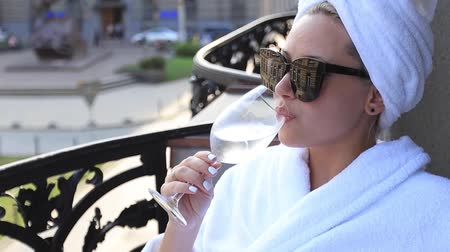 халат : elegant girl in a white bathrobe and a White towel on the head, enjoying a glass of white wine