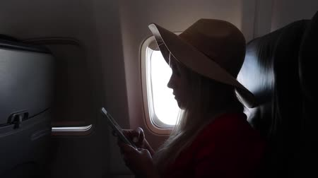Tourist woman in a hat sits near the window of an airplane at sunset and using a mobile phone while flying