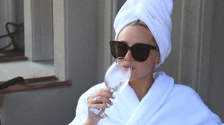 Beautiful blonde in white bathrobe and sunglasses enjoying a glass of champagne sitting on the hotel