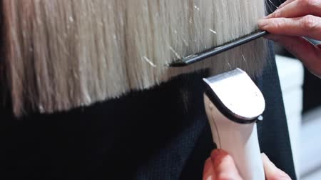 Hair cutting with hair clipper machine. Hairdresser do haircut closeup. split ends Cutting at home