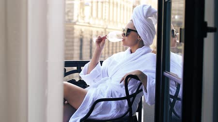 young woman, dressed in a white bathrobe, hair towel and sunglasses, sits on the balcony