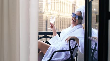 woman with a glass of champagne sitting on the balcony in a bathrobe with a towel on her head
