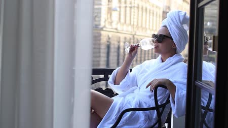 Beautiful young woman in white bath robe lying and drinking wine in hotel room. Relaxation
