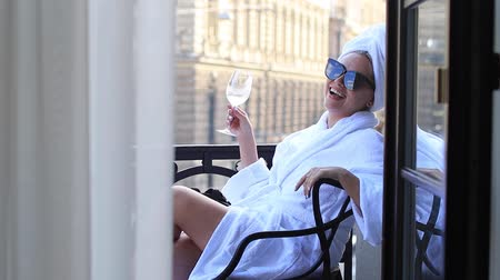 proposta : attractive woman in a white bathrobe and towel holding champagne glass and smiling for the camera
