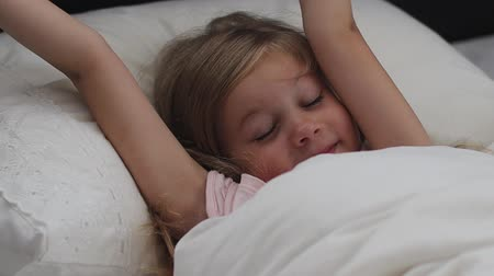 wakes : broken sleep. child insomnia. little girl waking up and tumble in bed