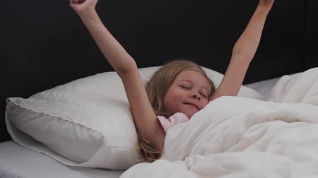 Happy girl child waking up stretching arms on the bed in the morning. Health, beauty and childhood