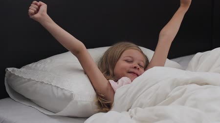 Child girl wakes up from sleep.A nice child girl enjoys sunny morning. Good morning at home Stok Video