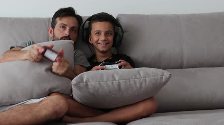 Father and young child are playing video game on couch at home