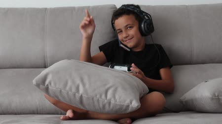 boy plays video games and talks on the smartphone, happily talks and smiles during a conversation.