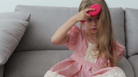 Cute little girl combing her blond hair with a brush