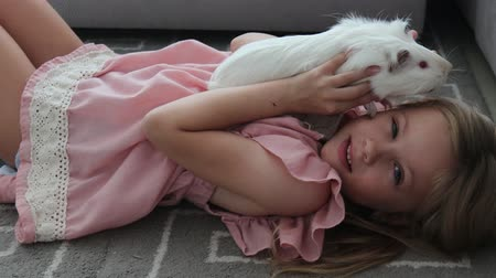 Home Animal Child Little Girl Plays Strokes Guinea Pig Pet Lying On The Floor Stok Video