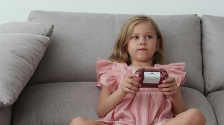 Anxious preteen girl in earphones sitting on sofa, holding joystick and paying video game