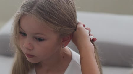 braids : Mom does the hairstyle of her little daughters tails