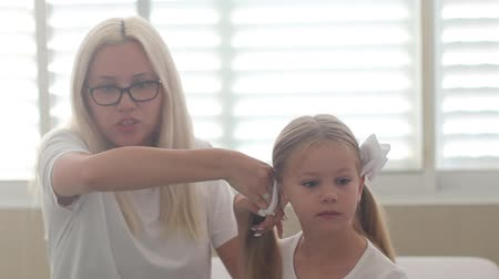 blue braid : Mom combs hair to a little girl with blue eyes Stock Footage