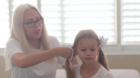 blue braid : Mom combs hair to a little girl with blue eyes slow motion Stock Footage